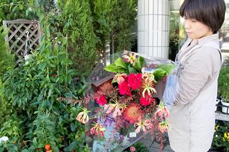 大人の雰囲気の色合いの、バラの赤が際立つ大きくボリュームのある花束です。